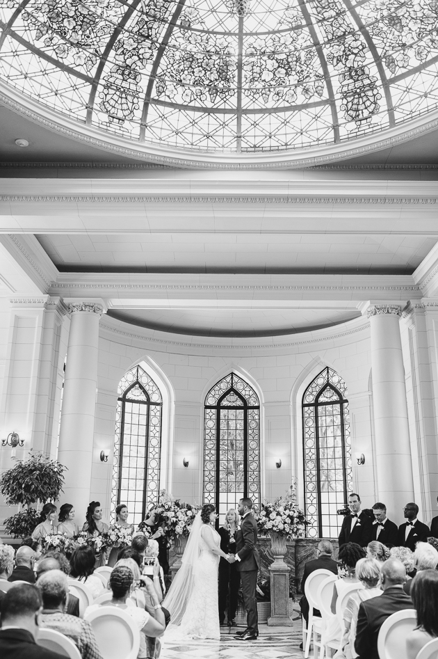 Casa Loma Wedding in Toronto with the groom and bride holding hands during their wedding ceremony beneath the stained glass dome of the conservatory.