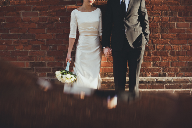 Candid Wedding Photographer. Portrait photography of the bride and groom against a brick background.