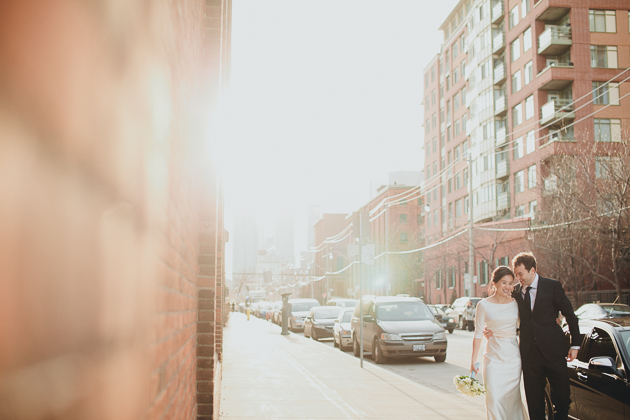 Candid Wedding Photographer. The groom and bride walk down the street arm in arm.