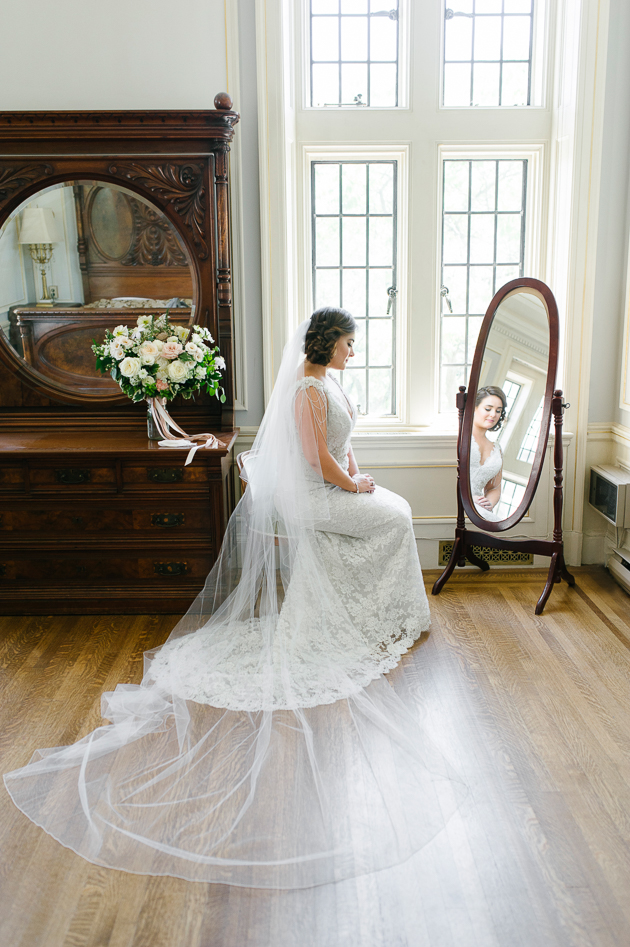 Casa Loma Wedding Toronto, capturing the beautiful bride sitting by a brightly lit window in Lady Pellatt's Suite.
