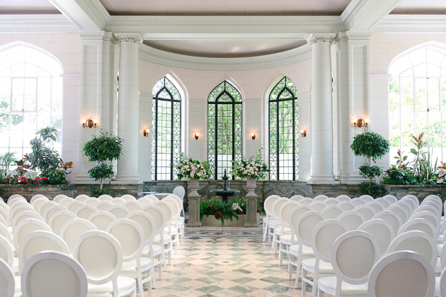 Casa Loma Wedding Toronto, wedding ceremony set up in the Conservatory. With beautiful tall arched windows, plenty of natural light, marble floors and flower beds this is a most photogenic and timeless venue.