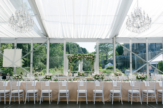 Casa Loma Wedding Toronto, inside the glass pavilion with beautiful communal table set up and crystal chandeliers with a view of the lush green estate gardens.