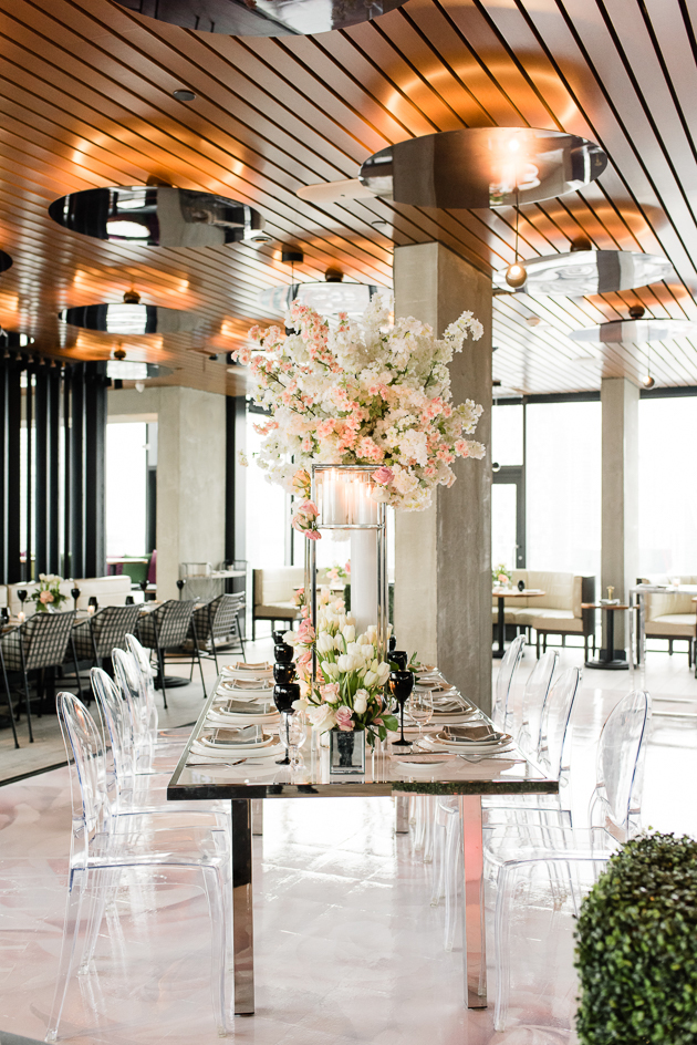 Lavelle Toronto Wedding Photography. Elegant rooftop experience in Toronto's King West neighbourhood. Wedding details photography of polished chrome table with Louis ghost chairs, tall floral centerpiece and candles.