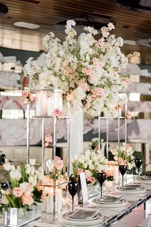 Lavelle Toronto Wedding Photography. Elegant rooftop experience in Toronto's King West neighbourhood. Wedding details photography of guest table settings with white and pink floral centerpieces, candles and white tableware.
