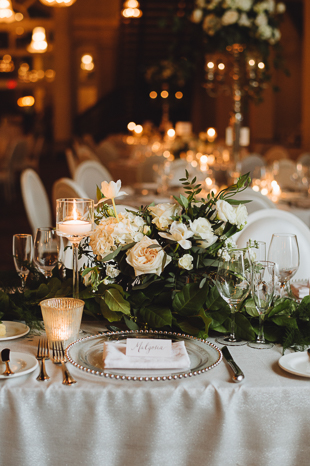 Liberty Grand Wedding Photography. Wedding details photography of guest table settings. Clear glass plates with white place setting napkins and florals.
