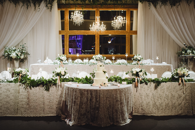 Liberty Grand Wedding Photography. Head table decorated with florals.