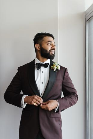 Toronto Wedding Details Photography. Groom getting dressed in his black and burgundy suit, black bowtie and white collared shirt.