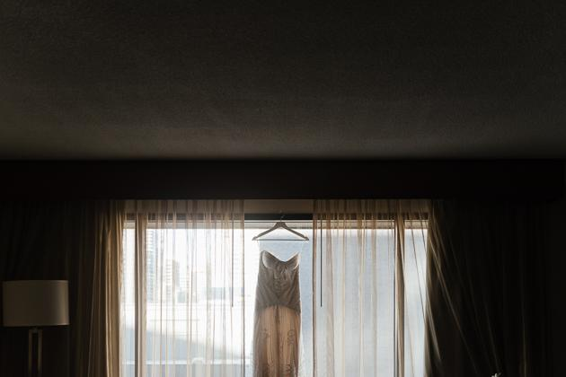 Toronto Wedding Photography. Bride getting dressed photo session. Hanging bridal gown.