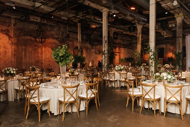 Fermenting Cellar Toronto Wedding Photographer. Tall floral centerpieces on white table cloths and cafe style bentwood dining chairs suit the dramatic industrial chic backdrop that is The Fermenting Cellar handsomely.