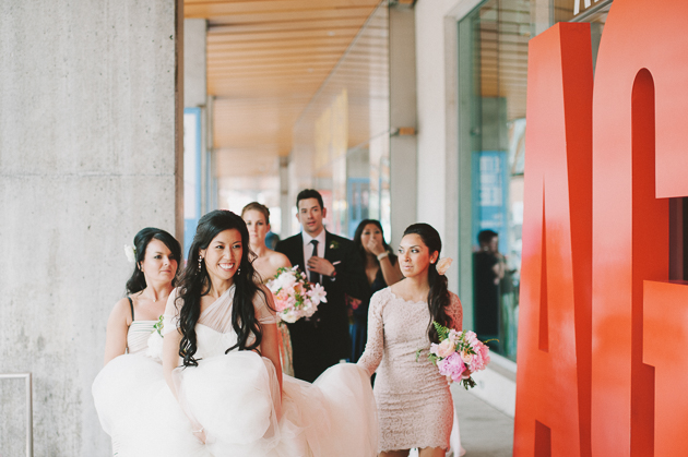 AGO Toronto Wedding Photography. The bridal party help carry the bride's train.