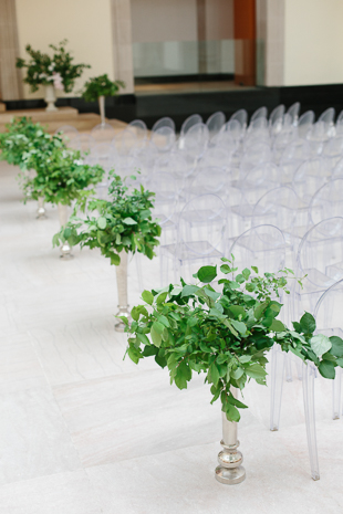 AGO Toronto Wedding Photography. The Art Gallery of Ontario makes a stunning and elegant backdrop for a couple's vows. Shown in this image are the Louis ghost guest chairs and green foliage in tall silver vases lining the aisle.