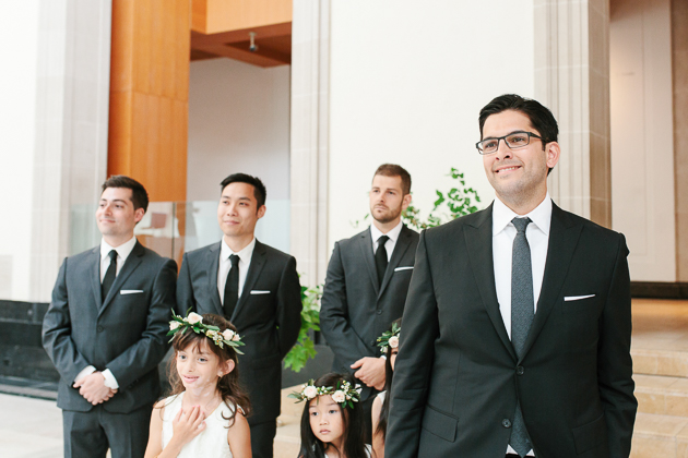 AGO Toronto Wedding Photography. The groom looks on with joy as his bride makes her way down the aisle.