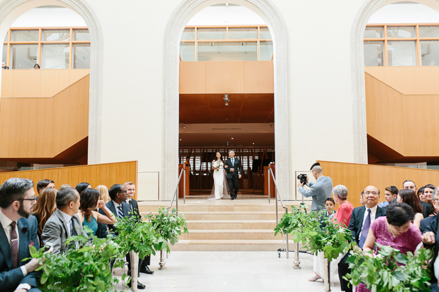 AGO Toronto Wedding Photography. The bride and her father arm in arm framed beneath a grand arch make their way down the aisle.