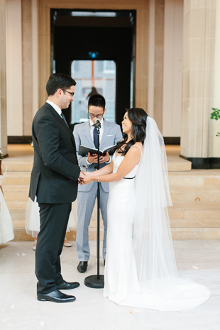AGO Toronto Wedding Photography. The bride and groom exchange their vows in the light filled lobby of the AGO beneath the iconic curved staircase.