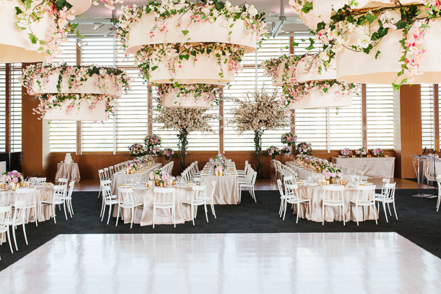 AGO Toronto Wedding Photography. Grand tiered pendants ornately decorated with florals hang above the dance floor where the couple will share their first dance.