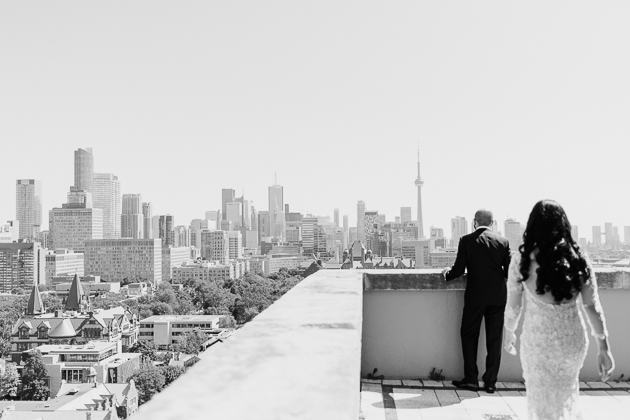 Park Hyatt Toronto Wedding Photography. The groom looks at the city view from the rooftop of the Park Hyatt hotel waiting to see his approaching bride for the first time.