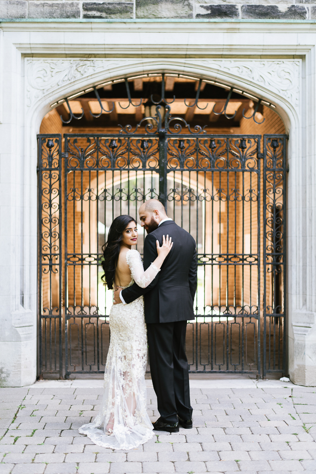 U of T Editorial Wedding Photographer. The bride and groom photographed outdoors on the beautiful UofT grounds framed by a carved limestone archway and wroght iron fence.