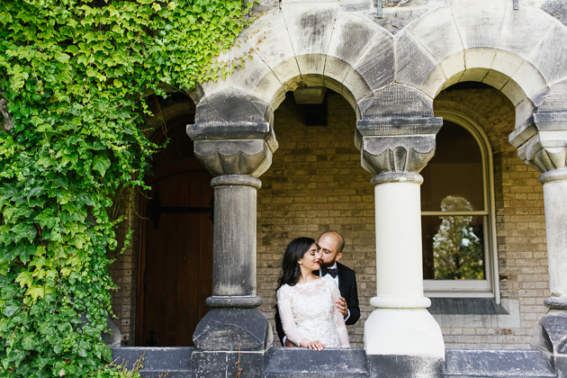 Editorial Wedding Photographer. The couple photographed outdoors under U of T stone arches.
