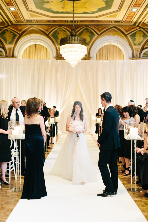 our beautiful bride walking down the aisle during their wedding ceremony at Fairmont Royal York