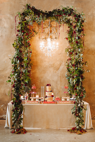 Fermenting Cellar Toronto Wedding Photographer. Floral wreath and chandelier envelope the wedding cake and sweets table.