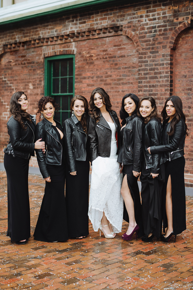 Fermenting Cellar Toronto Wedding. Outdoor creative portrait session with the bride and her bridesmaids styled in black dresses and black leather jackets in the Distillery District.