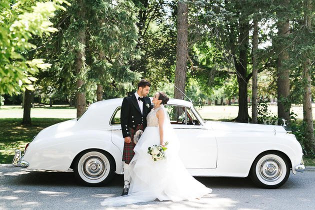 Eagles Nest Golf Club Wedding Venue. Toronto Photojournalistic Wedding Photographer. Creative portrait photography of couple standing in front of white vintage car.