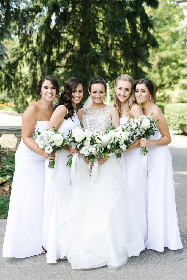 Eagles Nest Golf Club Wedding Venue. Toronto Photojournalistic Wedding Photographer. Portrait photography of the bridal party, the bride in a beautiful lace and chiffon ivory dress and her bridesmaids in white dresses.