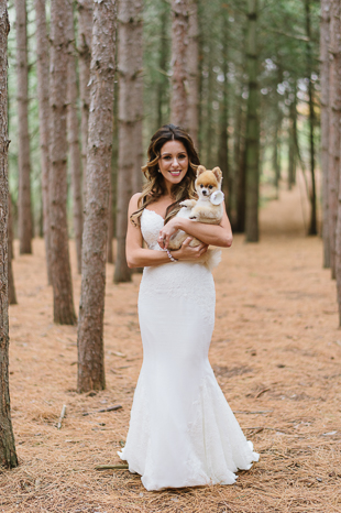 a bride holding her pretty dog during the wedding photo shoot