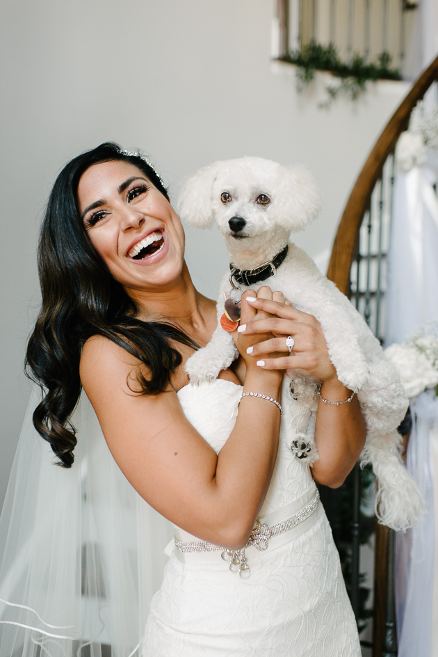 a happy bride holding her favourite dog on a wedding day