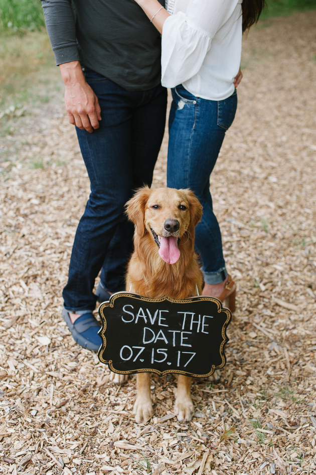 a couple and their dog holding a Save The Date sign