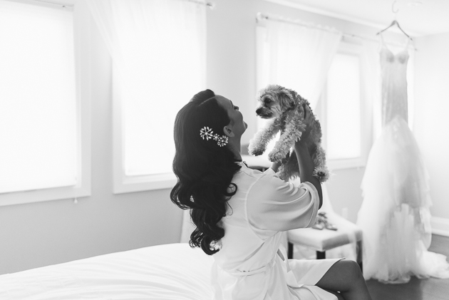 a happy bride holding her favourite dog in the morning of her wedding day