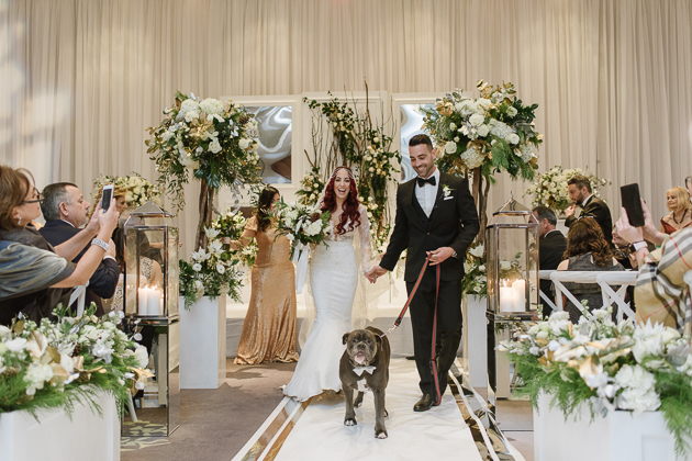 happy bride and groom walking down the aisle with their favourite dog