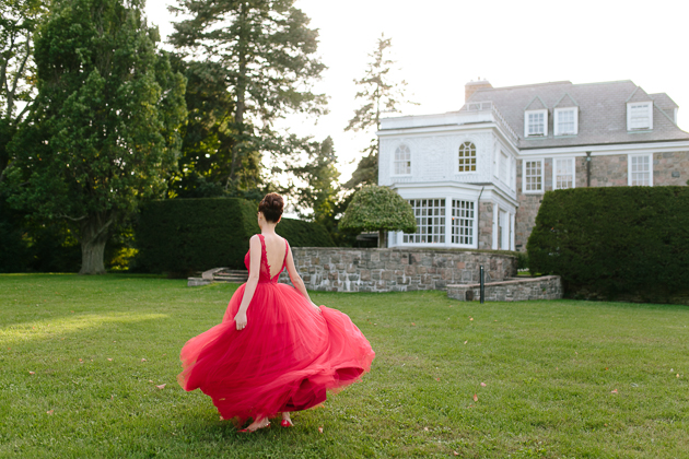 Estates of Sunnybrook Wedding Venue Photography. Outdoor creative photo session with bride twirling in her beautiful red chiffon dress on the estate grounds just before sunset.