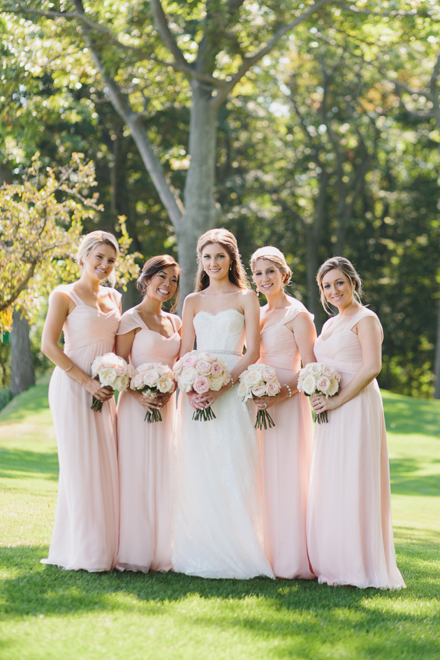 A bride and her beautiful bridesmaids in blush pink dresses