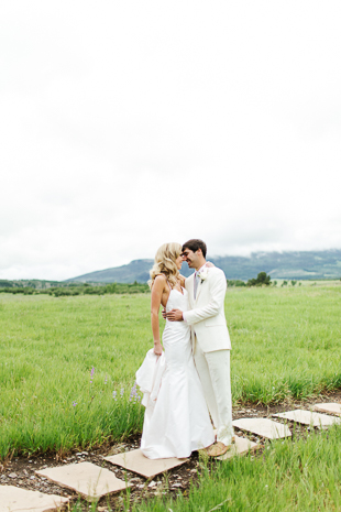 A bride and groom standing in front of the mountains in Colorado