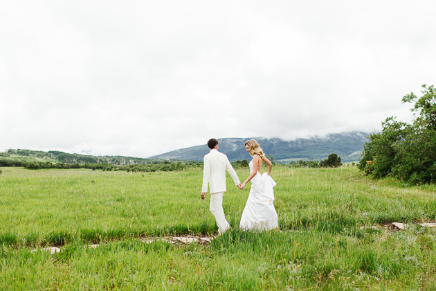 a bride and groom walking towards their wedding ceremony location in Colorado