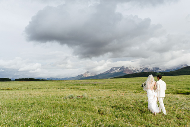 A bride and groom walking hand in had at their Colorado wedding