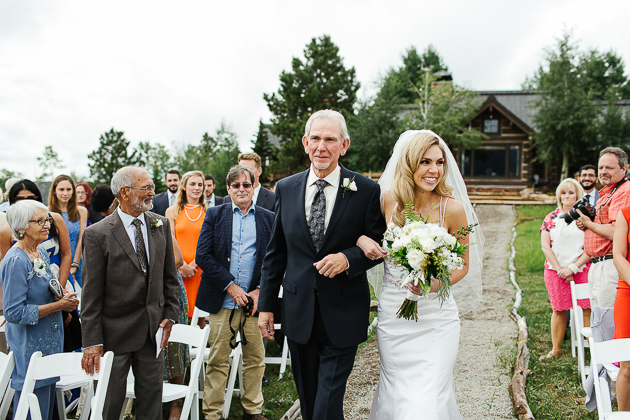 A bride walking down the aisle accompanied by her happy father. Colorado Wedding Photography
