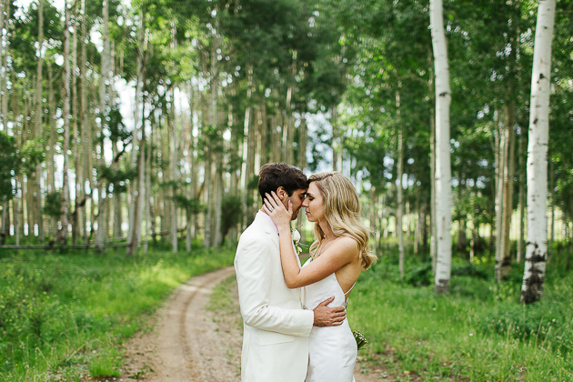 A bride and groom kissing in the forest of Colorado