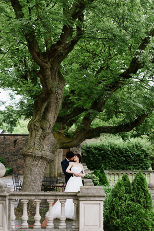 A bride and groom kissing under the towering tress at Graydon Hall Manor wedding