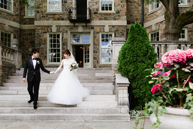 A groom leads the bride's way during their wedding photography session at Graydon Hall Manor