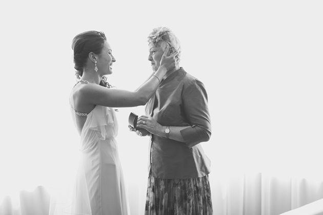A bride holds her mother as she gives her a wedding day gift