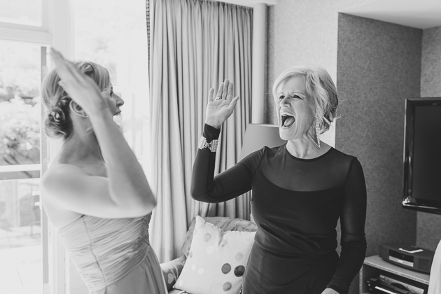 A mother giving high-five to one of the bridesmaids during the bride's getting ready photos in the morning
