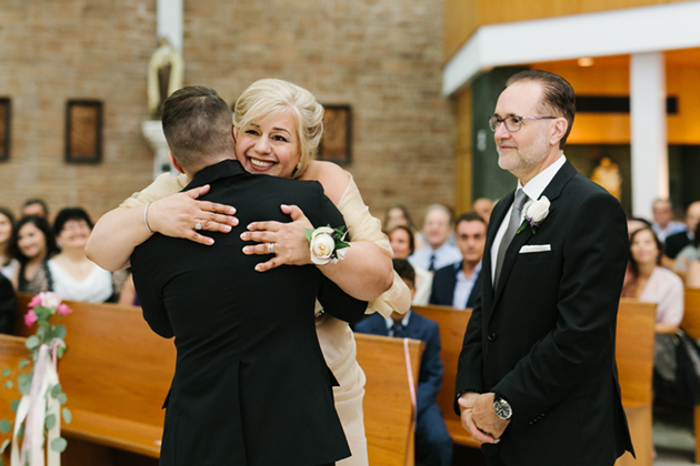 A happy mother-of-the-groom gives her son a big hug before the wedding ceremony