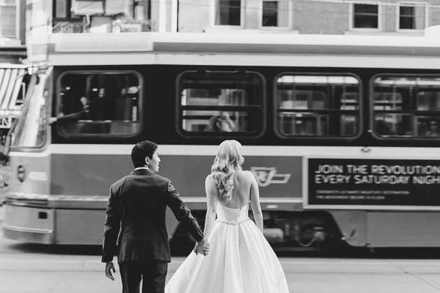 A bride and groom crossing the street during their creative wedding photography in downtown
