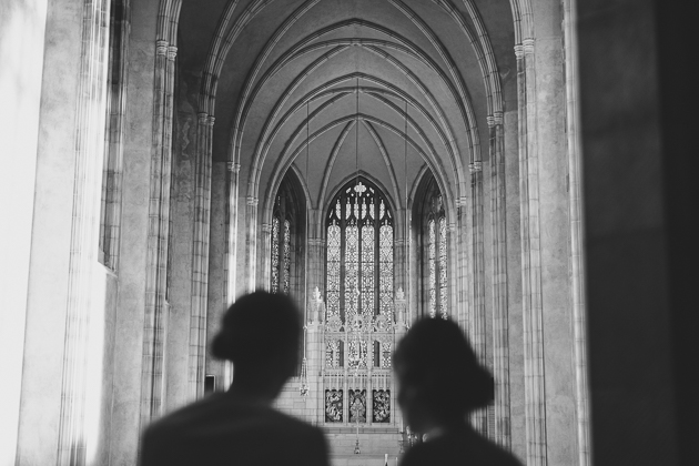 Two bridesmaids looking out at the wedding ceremony in the chapel