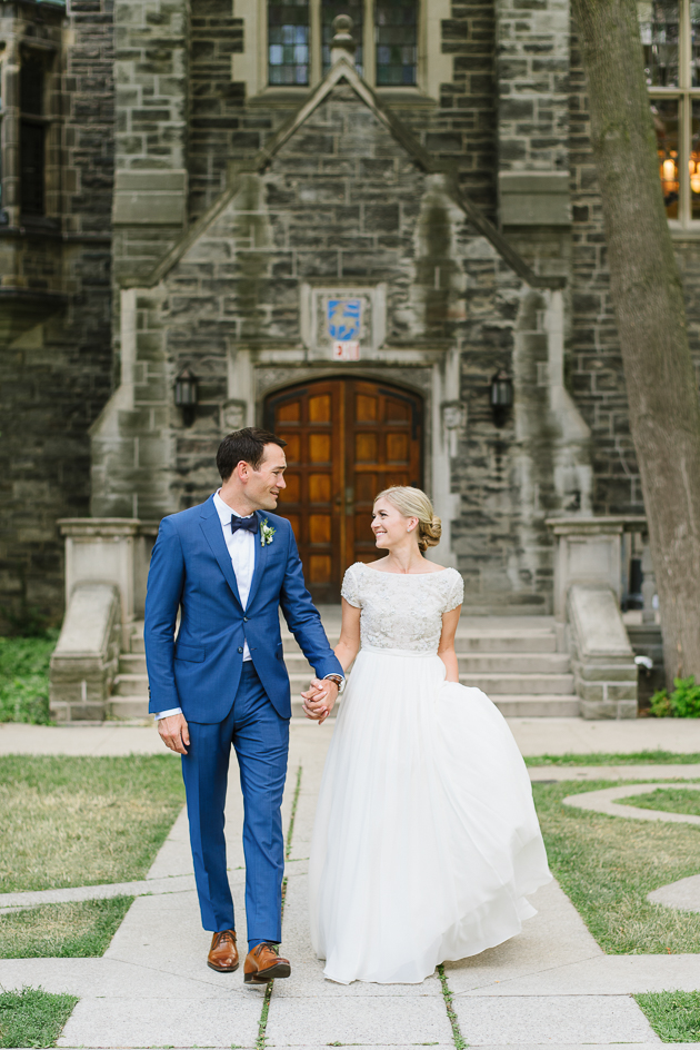A bride and groom walking towards their wedding ceremony during their wedding photoshoot at the U of T