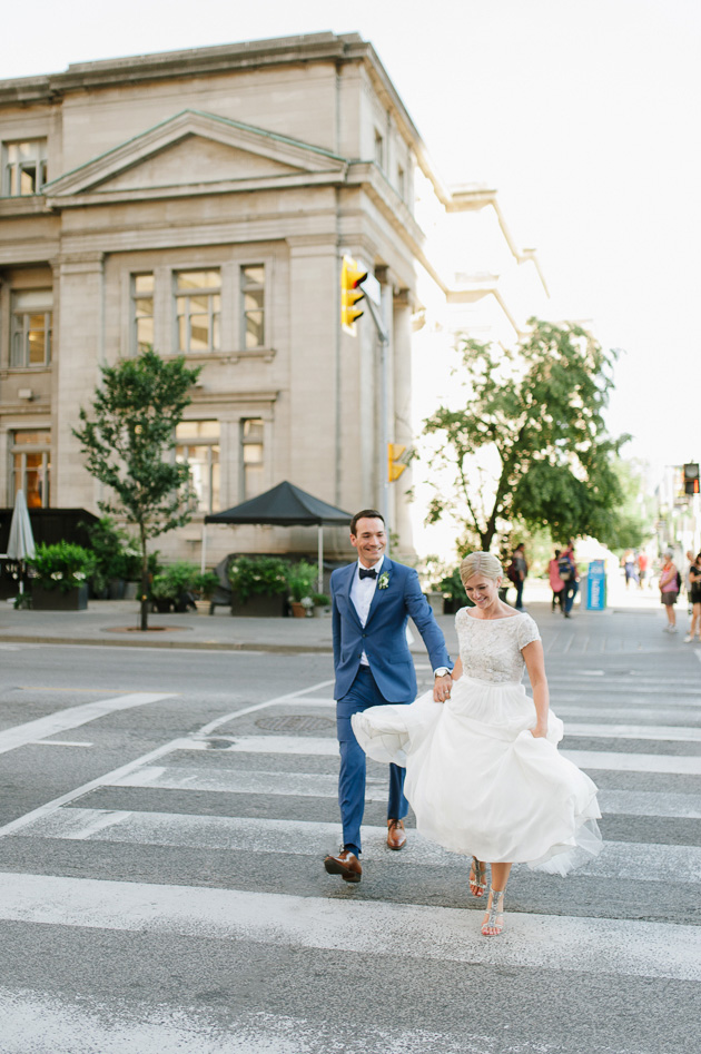 A bride and groom crossing the street in downtown Toronto right after their wedding ceremony