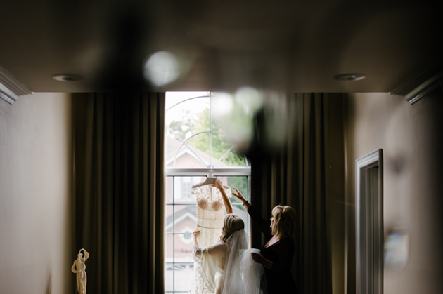 A bride and mother-of-the-bride are lifting the wedding dress
