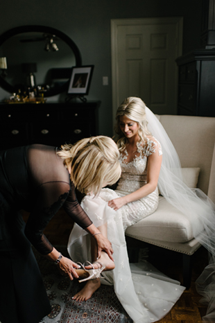 Mother-of-the-bride helping her daughter put on her wedding shoes